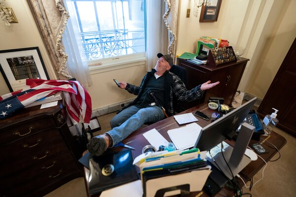 Richard Barnett of Gravette, Ark., posed for photographs while sitting at a desk in Speaker Nancy Pelosi's office during the siege at the Capitol.
