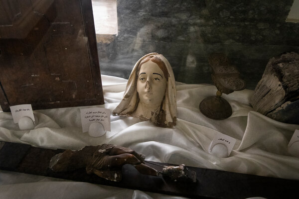 Statues broken by ISIS in a glass case at St. George church in Bartella.
