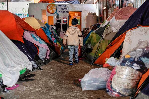 A migrant boy walks amid tents at the Juventud 2000 migrant shelter in Tijuana, Mexico.