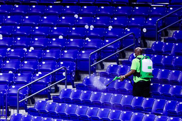 Un impiegato del Lucas Oil Stadium che disinfetta i sedili tra una partita e l'altra durante il secondo turno del torneo di basket maschile dei Big Ten.