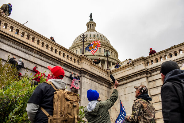A mob of Trump supporters climb the walls of the U.S. Capitol on Jan. 6. The Justice Department is weighing sedition charges against some of the rioters, according to law enforcement officers briefed on the deliberations.