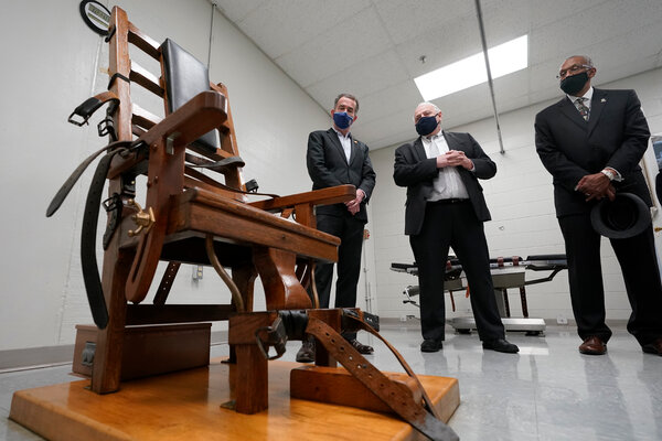 Gov. Ralph S. Northam, left, looks over the electric chair in the death chamber at Greensville Correctional Center in Jarratt, Va., on Wednesday prior to signing a bill abolishing the death penalty.