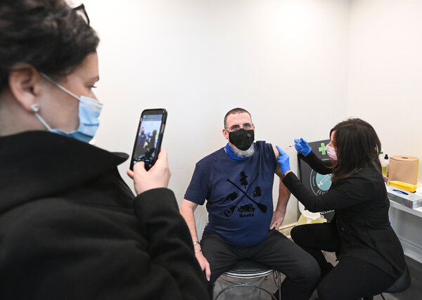 Sandra Medeiros taking a photo of her husband, Daryl Bedard, as he received the AstraZeneca vaccine in Toronto this month.