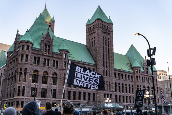 Protestors passed Minneapolis City Hall on Monday on the way to the Hennepin County Government Center, where the Derek Chauvin trial was beginning.