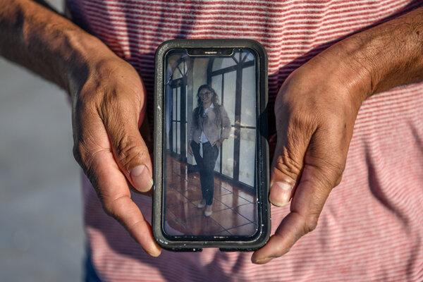 Mr. Melendrez holding a phone with a photograph of his daughter, Yesenia Magali Melendrez Cardona.