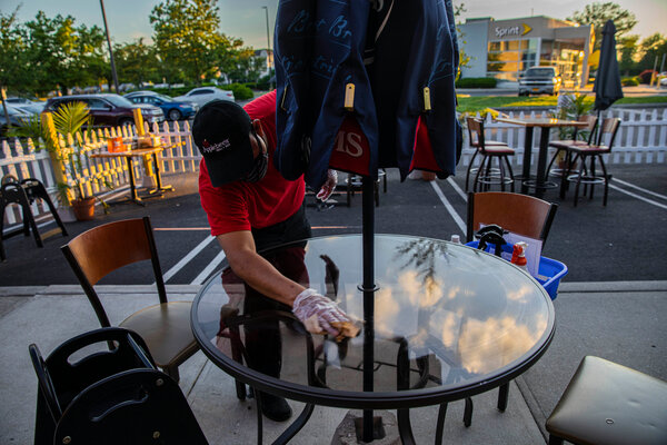 A worker disinfected a table at a restaurant in Westbury, N.Y., last year.
