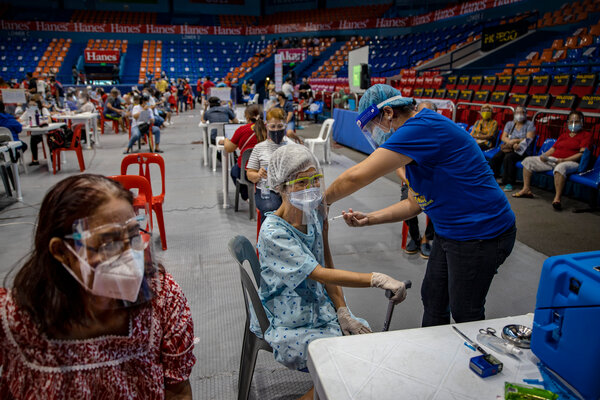 Administering the AstraZeneca vaccine at a sports arena inSan Juan, Philippines, last month.