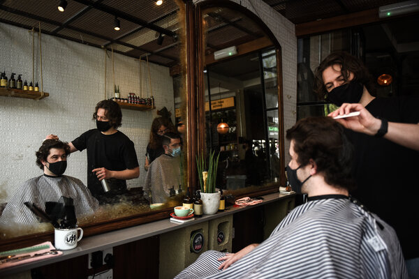 Customers enjoyed their first haircuts in several months at a barbershop in London on Monday.