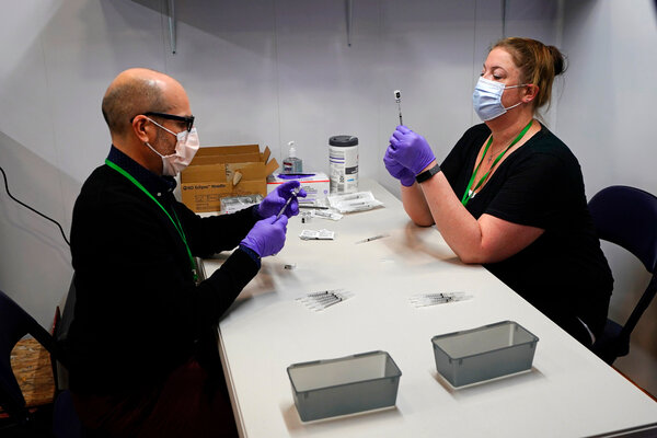 Pharmacy technicians filling syringes with vaccine in Portland, Maine, this month.