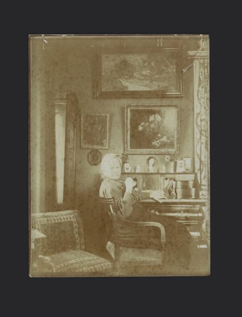 """Jo van Gogh-Bonger at her desk in Amsterdam, sometime after 1909. Vincent van Gogh's """"Vase of Honesty"""" (1884, left) and Henri Fantin-Latour's """"Flowers"""" hang beneath Vincent's """"Landscape at Twilight"""" (1890)."""
