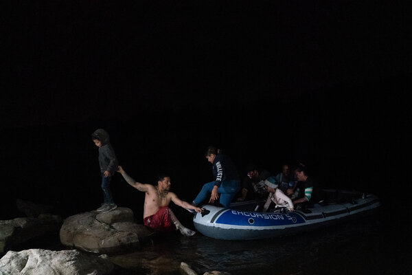 A coyote helping migrants onto the U.S. shore after safely crossing a stretch of the Rio Grande near Roma, Texas.