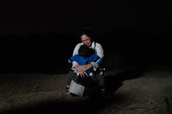 A woman and her child weeping with relief after safely arriving on shore.