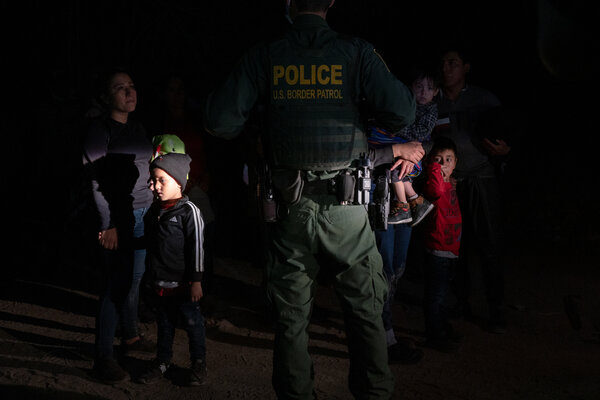 Migrants being met by a Border Patrol agent after walking up from the Rio Grande.