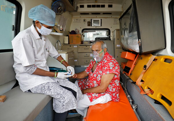 A paramedic checking the oxygen level of a patient inside an ambulance in Ahmedabad, India, on Thursday.