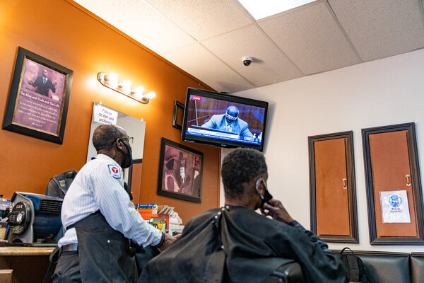Patrons and employees at Urban Touch Barbers & Salon watch the trial of Derek Chauvin on televisions.