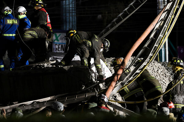 Mexican rescue personnel removing a victim's body from the train wreck.