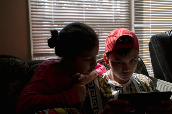 Melissa and her brother, Yeison, playing together on a tablet.