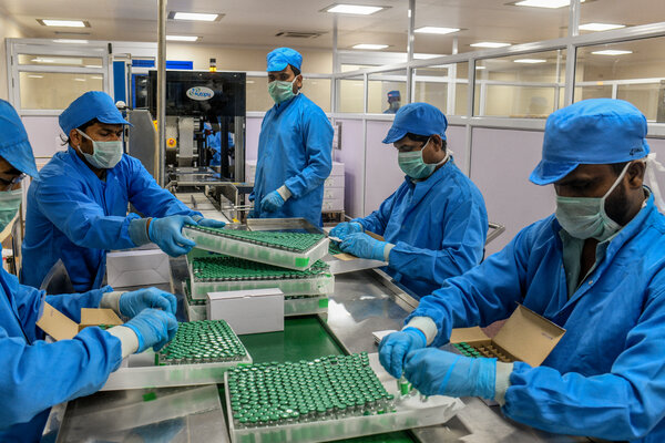 Workers with vials of vaccine at a production facility of the Serum Institute of India in January.