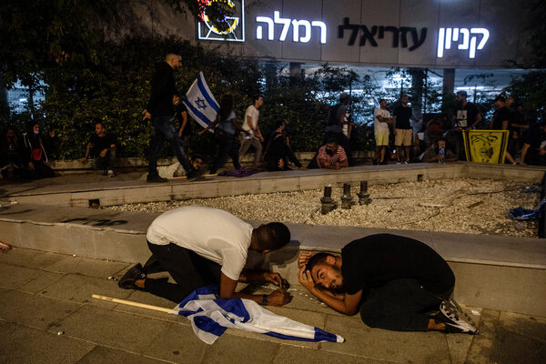 Jewish nationalist demonstrators take cover as rockets fired from the Gaza Strip head toward the Israeli town of Ramla, on Tuesday.