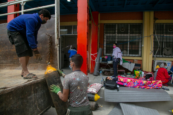 Unloading an oxygen cylinder as a patient lay outside the emergency ward of a hospital in Kathmandu, Nepal, on Monday.