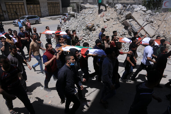 Palestinians on Saturday carried the bodies of children killed in an Israeli airstrike on a refugee camp in Gaza.
