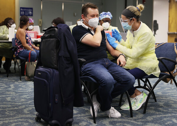 A traveler from Mexico received a dose of the Pfizer vaccine this month at Miami International Airport.