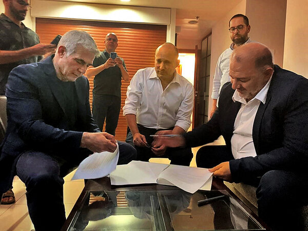 Mansour Abbas, the leader of the Arab party Raam, signing a coalition agreement with Yair Lapid, left, and Naftali Bennett.