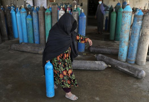 """Carrying an oxygen cylinder from a privately owned factory in Kabul, Afghanistan, on Saturday. """"There is more need for oxygen, and the number of patients is too high,"""" an adviser to the Ministry of Public Health said."""