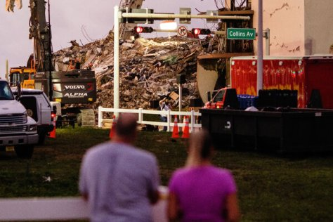 A couple looks over to the remains of the collapsed portion of the Champlain Towers South in Surfside, Fla., on Sunday morning.