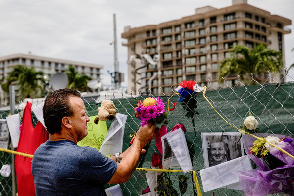 Chris Jeffers placed flowers on a barricade fence that has become a makeshift memorial near the site of the Champlain Towers South collapse site in Surfside, Fla.