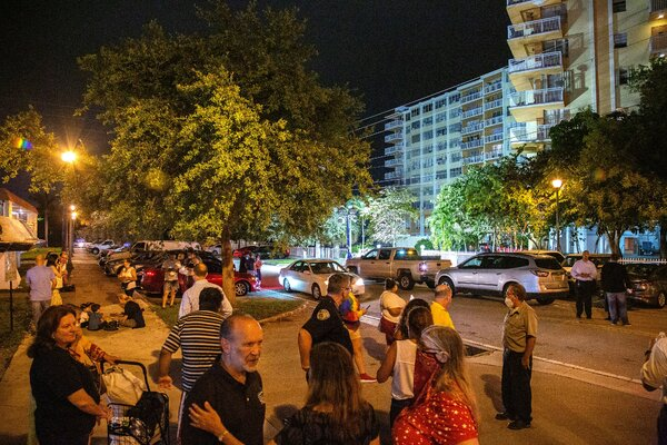 Residents of Crestview Towers condominium stood outside the building on Friday as it was being evacuated. The city of North Miami Beach deemed the building unsafe after receiving an engineer's report outlining structural and electrical problems.