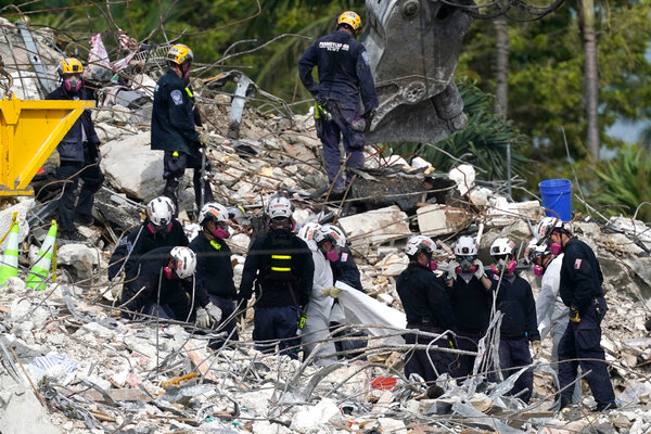 Rescue workers used a tarp to cover the remains of victims found at the site of the collapsed Champlain Towers South condo building on Monday.