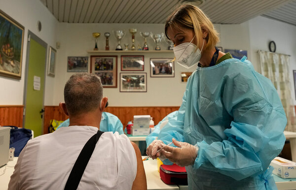 A medical worker administered a shot of the Johnson & Johnson vaccine to Fulvio Fraschini at a cultural center on the outskirts of Milan, Italy, on Wednesday.