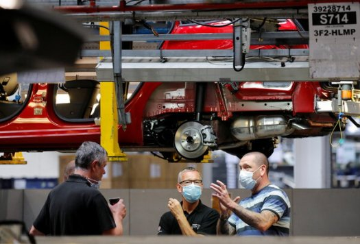 Workers an assembly line for Vauxhall, a Stellantis brand, in Ellesmere Port, England. Stellantis said sales rose 46 percent in the first half of the year.