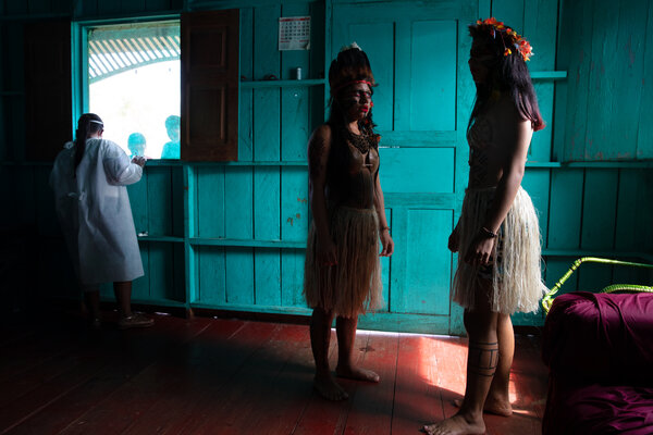 Indigenous people in Brazil's Amazonas State, dressed to welcome a medical boat that arrived in their remote area to offer coronavirus testing and other health care. At left is a nurse from the team.