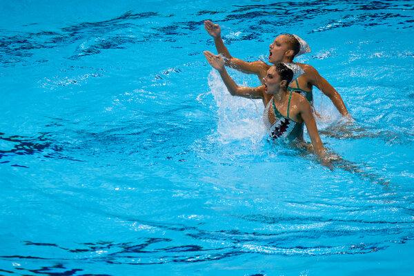 Maria Alzigkouzi Kominea and Evangelia Papazoglou of Greece compete in synchronized swimming at the Tokyo Aquatics Center on Monday.