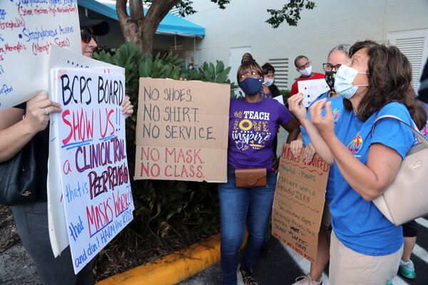 Teachers speak with anti-mask protesters about mask mandates outside of a Broward County School Board meeting, in Fort Lauderdale, Fla., last week.