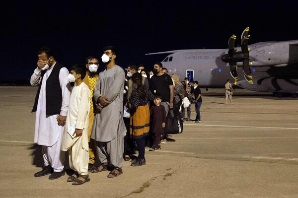 Afghans waiting on the tarmac after landing at the Torrejon military base in Spain early Thursday.