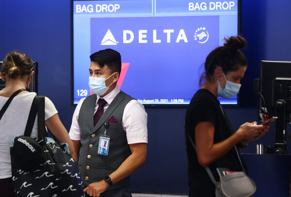 A Delta Air Lines counter at Los Angeles International Airport on Wednesday. Starting Nov. 1, employees who have not received a vaccine will have to pay an additional $200 per month to stay on the company's health plan.