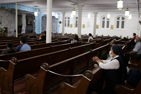 Parishioners during Thursday evening Spanish mass at Our Lady of Lourdes Church in Harlem. Many pews are blocked to create spacing due to Covid-19.