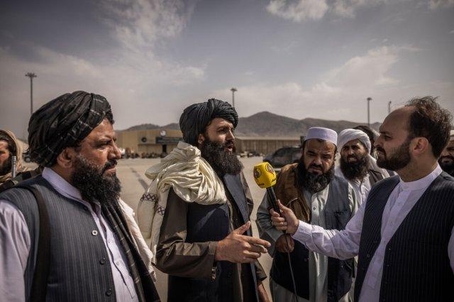本周,在喀布尔机场,与记者交谈的塔利班成员。