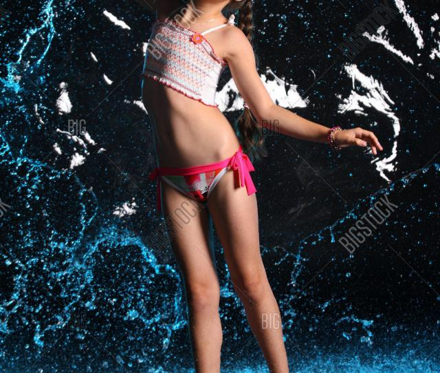 Adorable Young Teenage Girl In A Swimsuit Stands Barefoot In Splashing Water Pretty Child With