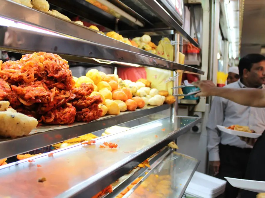 People help themselves to fried pakora (vegetables) and other fried Indian treats.