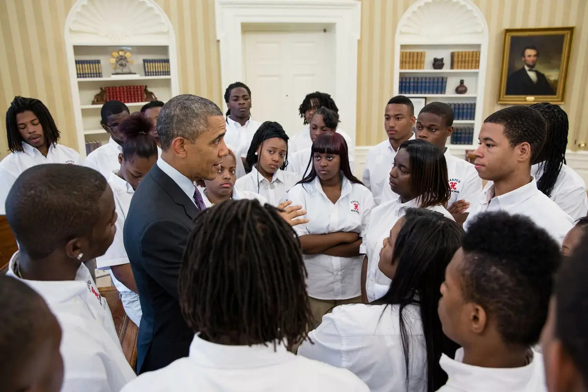 Obama talks with students from William R. Harper High School in Chicago, Ill., in the Oval Office.