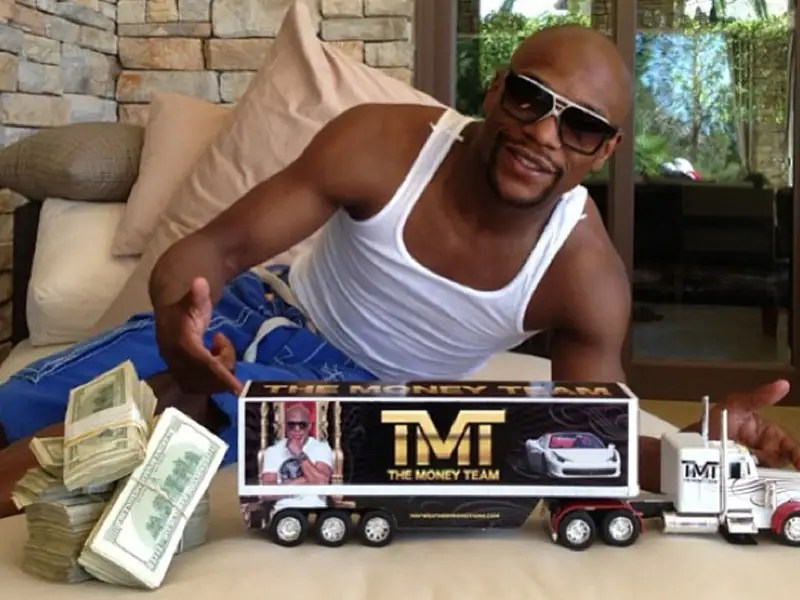 "His ""The Money Team"" Hess truck next to stacks of cash."