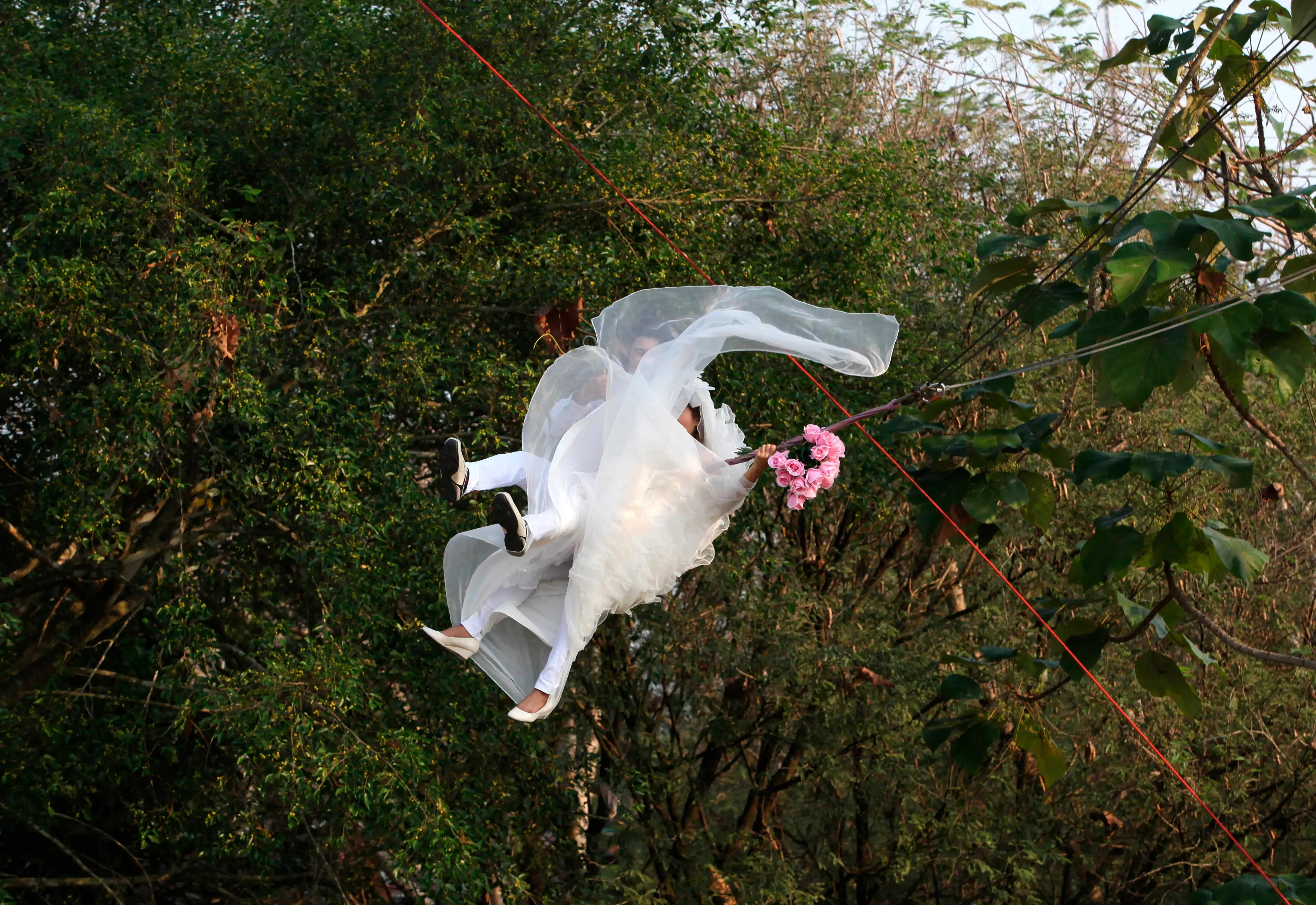 Prasit Rangsiyawong and his bride Varuttaon Rangsiyawong fly while attached to cables during a wedding ceremony in Prachin Buri province, east of Bangkok, Thailand.