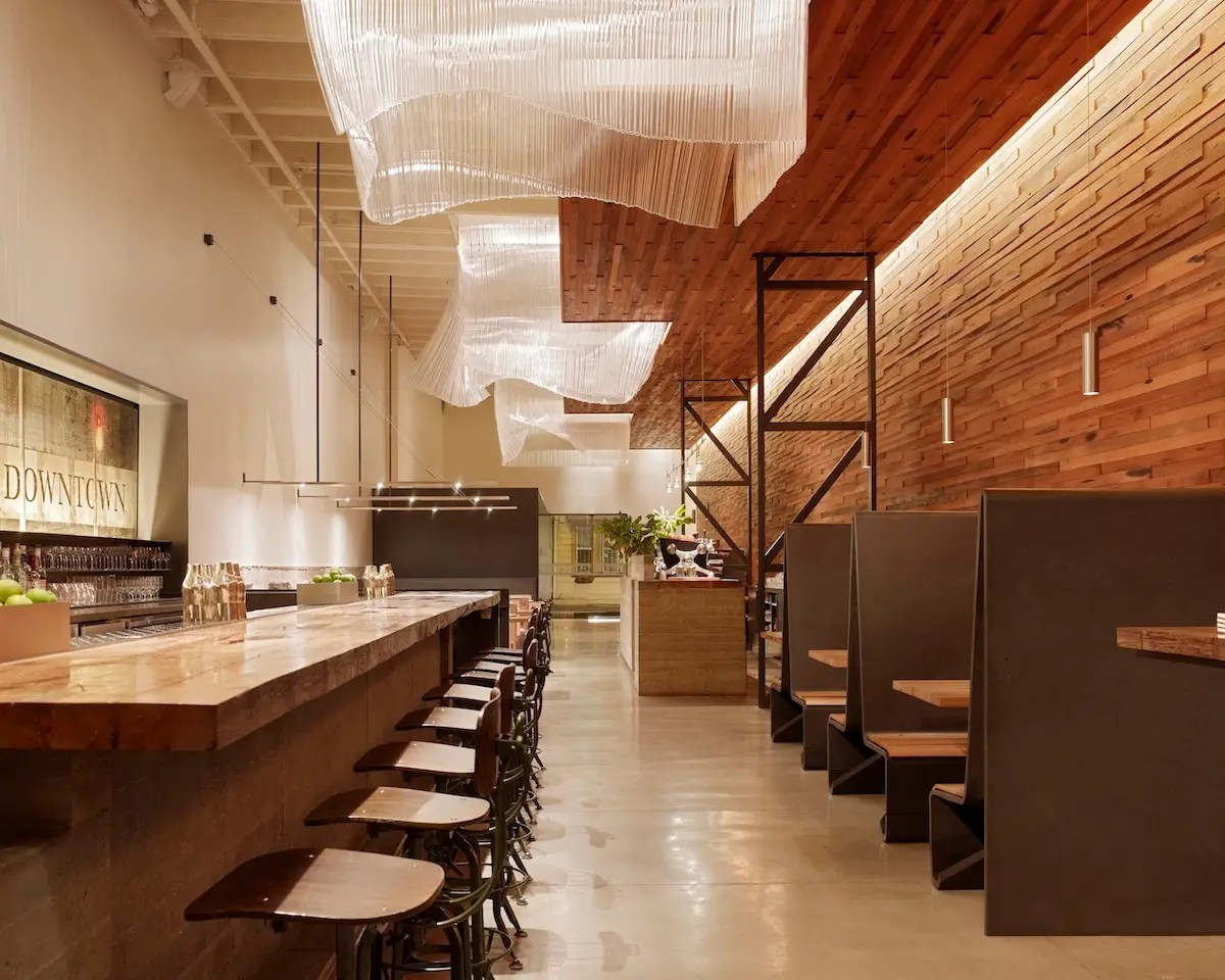 Bar Agricole is a 1,400-square-foot restaurant in San Francisco's South of Market neighborhood. The wooden interior wall is made of reclaimed whiskey-barrel oak, while the two bars consist of board-formed concrete and old barn beams (Aidlin Darling Design).