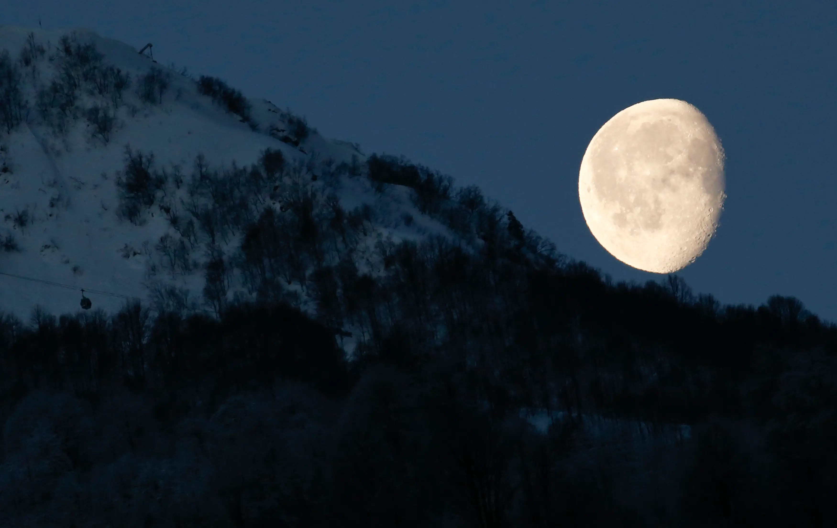 The moon is pictured above the mountains in Rosa Khutor in Russia during the 2014 Sochi Olympics.