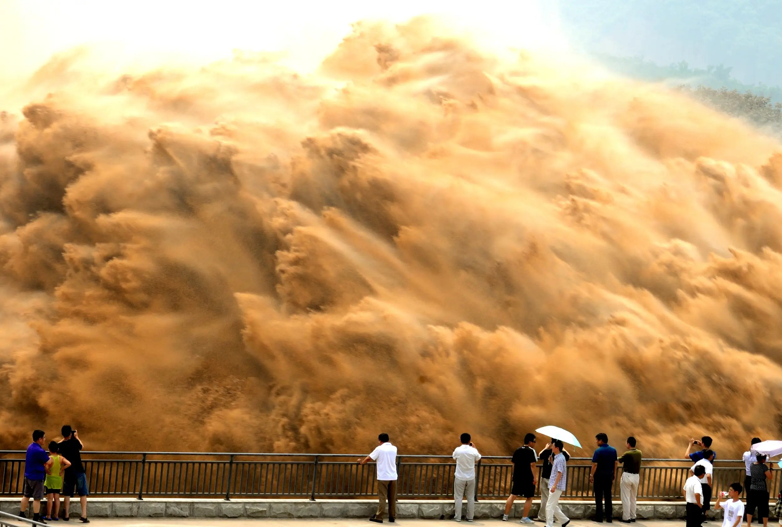 Visitors watch water gushing from the section of the Xiaolangdi Reservoir on the Yellow River during a sand-washing operation.