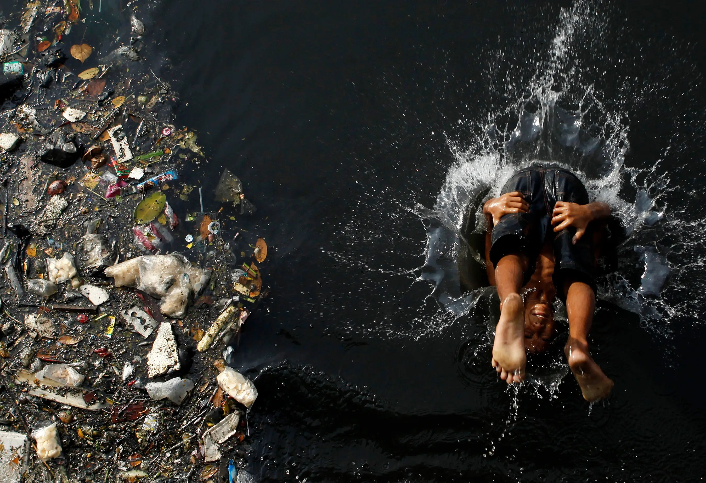 As our world grows, it's becoming disturbingly polluted. This boy cannonballs into a polluted river in Jakarta, Indonesia, while piles of garbage drift by next to him.